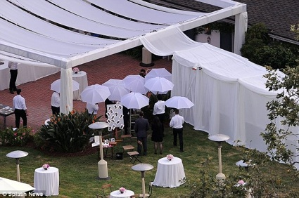 The guests use white umbrellas to shield themselves from prying paparazzi.