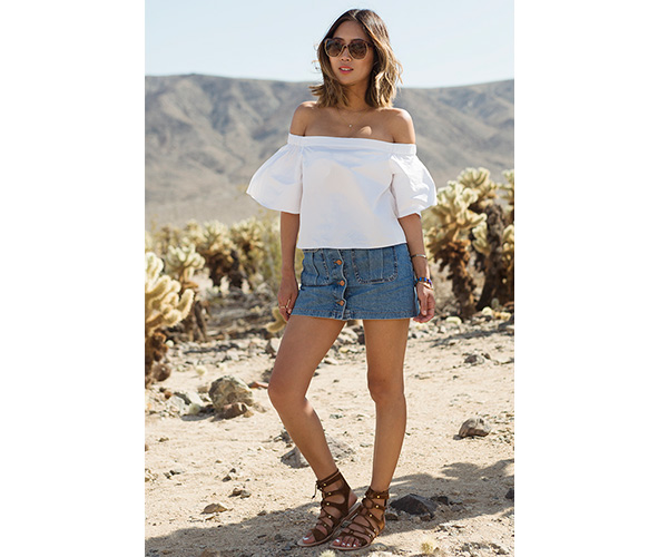 woman wearing white off the shoulder shirt with denim skirt and sandals