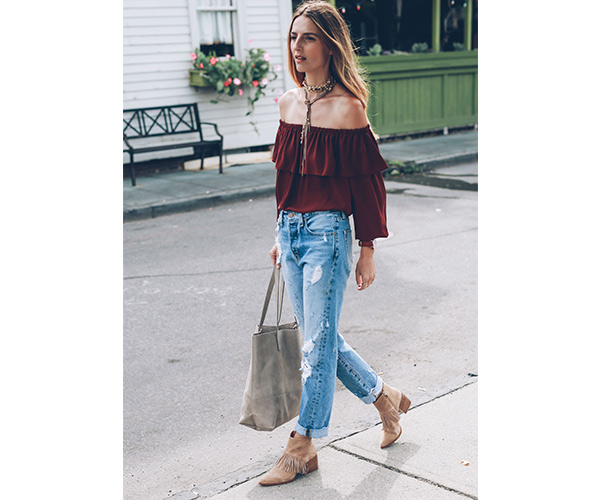 woman wearing a red off the shoulder top with tan stacked heeled booties