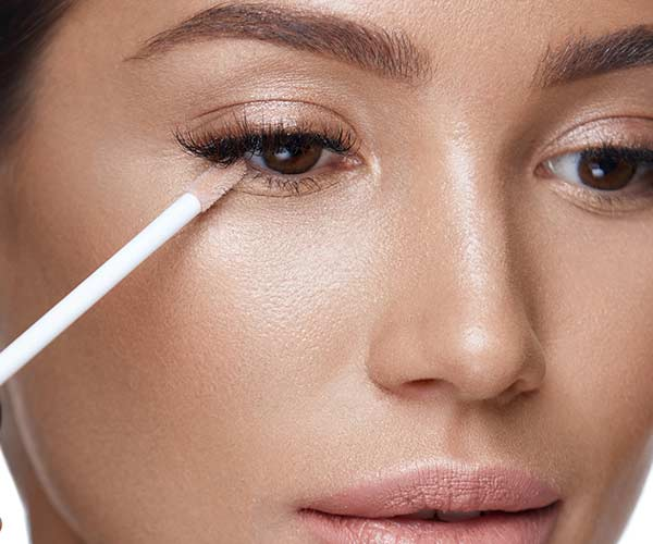 woman applying concealer