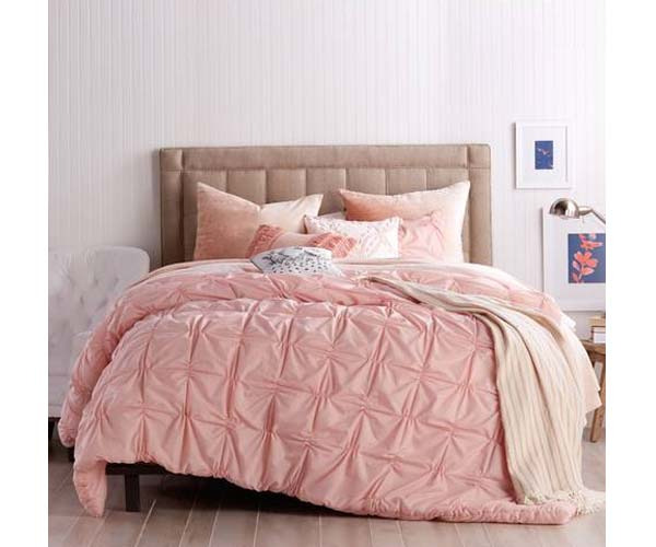 large bed with pink comforter and pillows