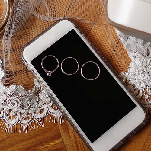 iphone on table with wedding rings on screen