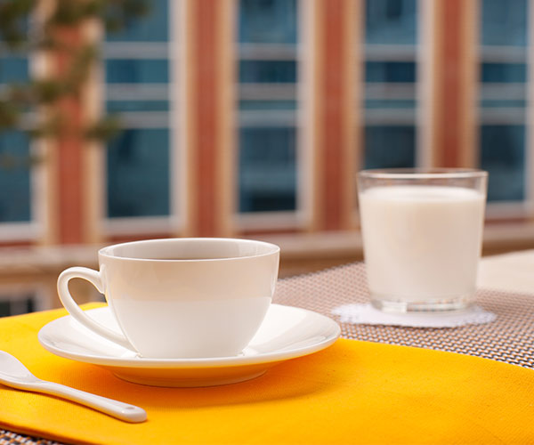 coffee on a table with glass of milk