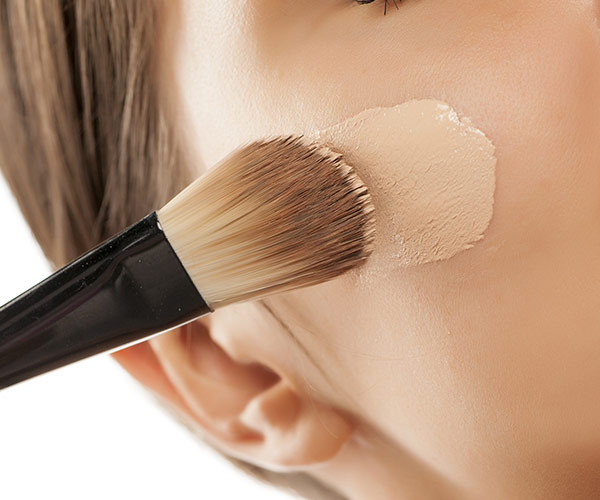woman applying foundation to face