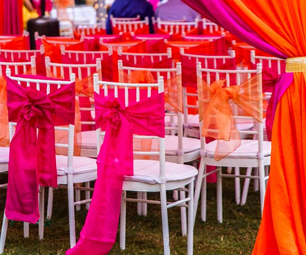 outdoor wedding chairs with neon and pastel ribbons