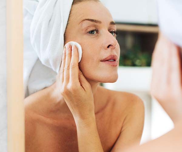 woman applying skincare product in bathroom mirror