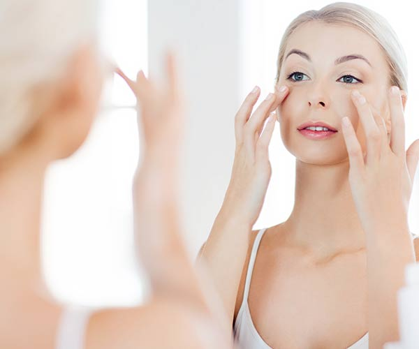 woman using skincare product in mirror
