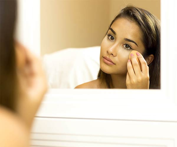 woman applying foundation in the mirror