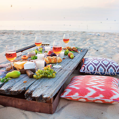 beach picnic table with food and floor pillows