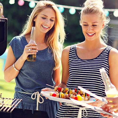 women at barbecue eating food