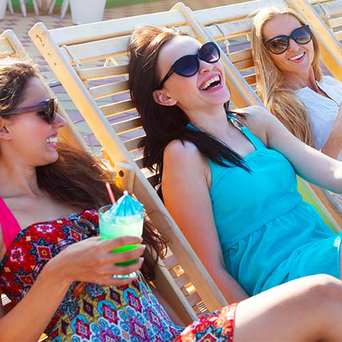 girls on lounge chairs at pool