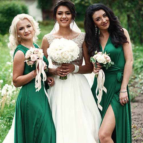 bride posing with bridesmaids outside