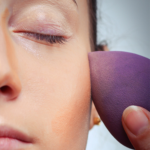 woman applying foundation with purple beautyblender