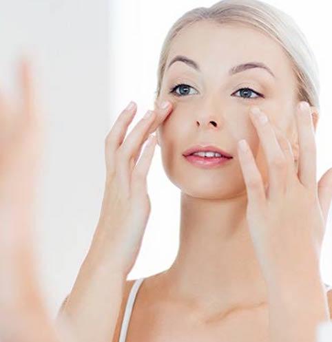 woman applying under-eye cream in mirror