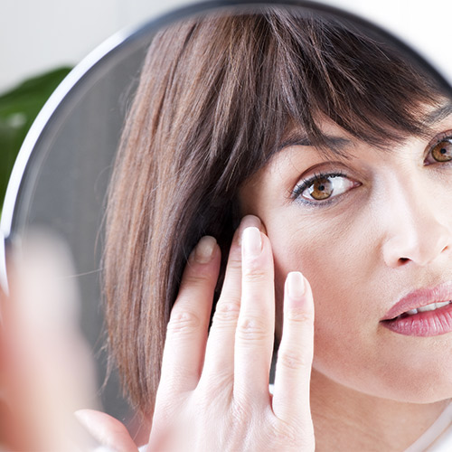 woman applying skincare products in mirror