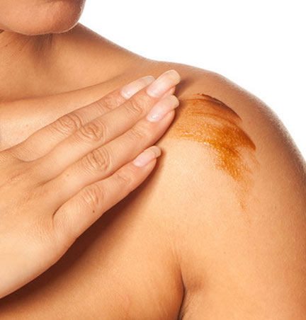 woman applying self-tanner to shoulder