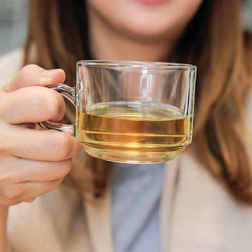 woman drinking white tea in a glass mug