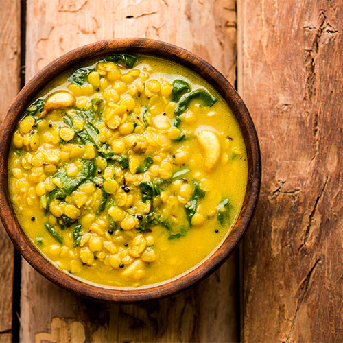 A bowl of dal and kale soup.
