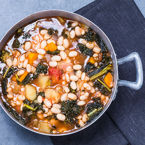 A bowl of bean and kale soup.