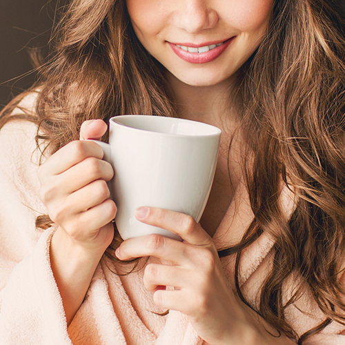 Woman holding a white mug.