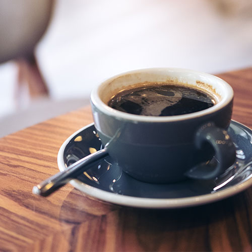 A cup of coffee in a blue mug.