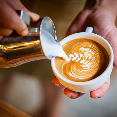 A person pouring froth on a latte.