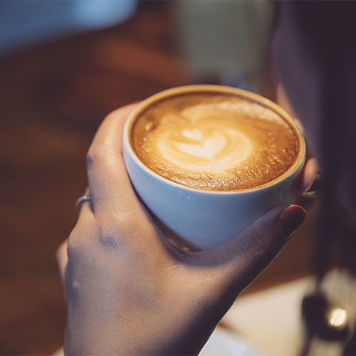 A person holding a latte.