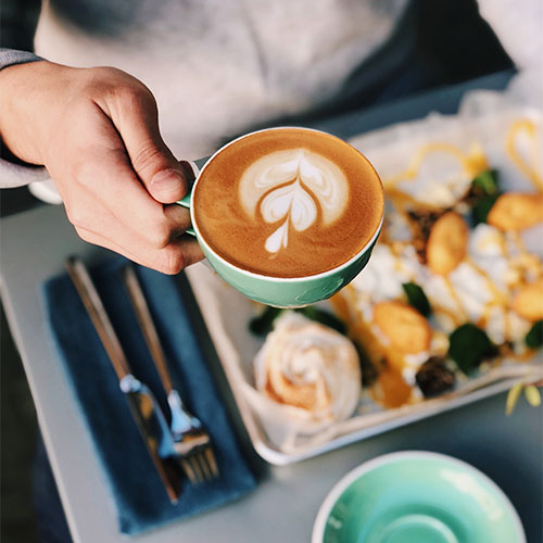 A person holding a latte with breakfast.