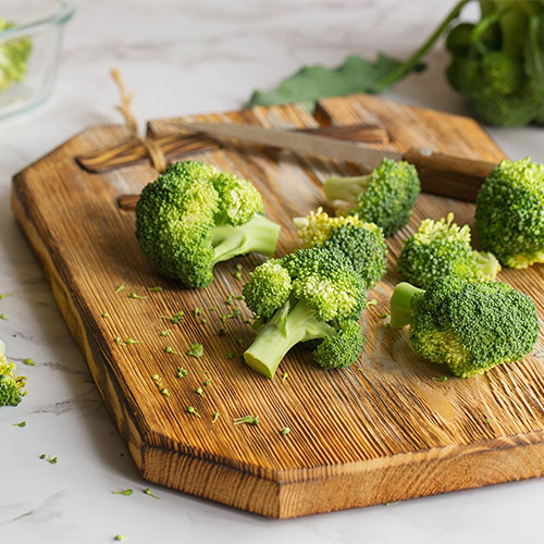 Broccoli florets on a wood board.