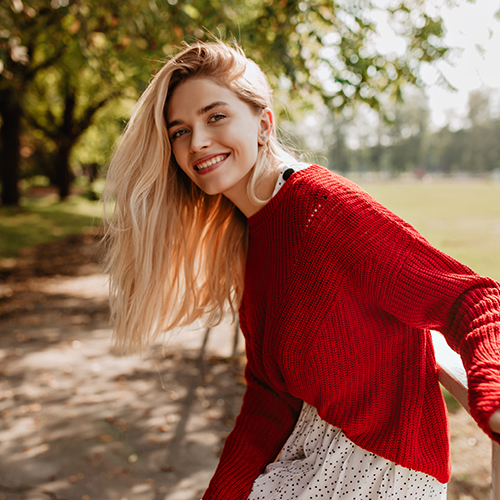 A woman in the outdoors wearing a red sweater.