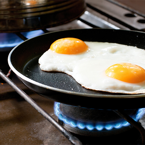 Eggs frying in a skillet.