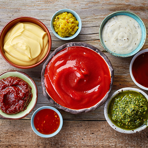 Various condiments and sauces in bowls.
