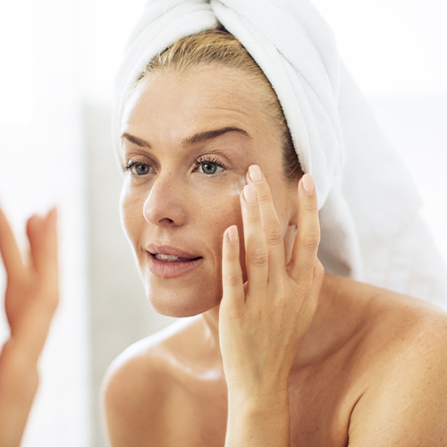 applying moisturizer in mirror