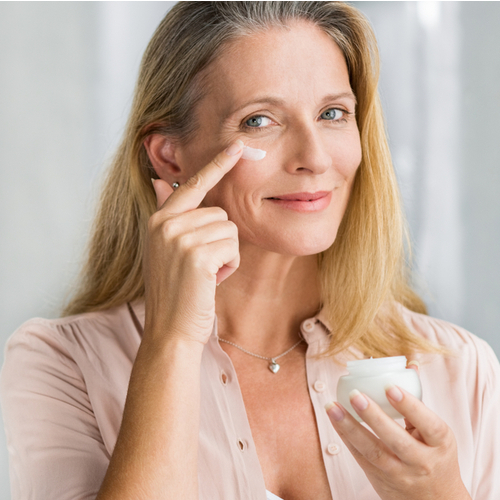 older woman applies eye cream