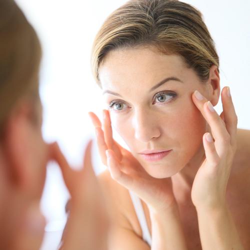 woman touching skin around her eyes