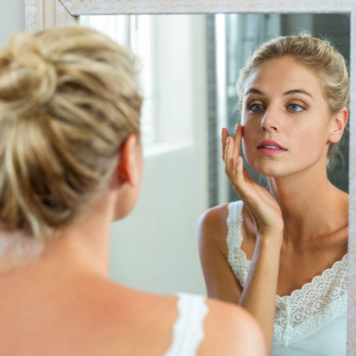 woman checking her face in mirror