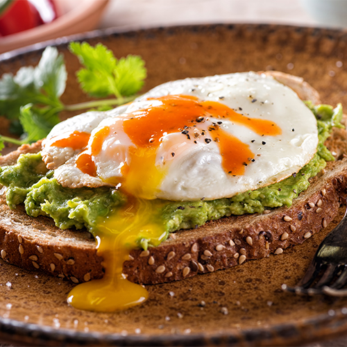 hot sauce and eggs on avocado toast