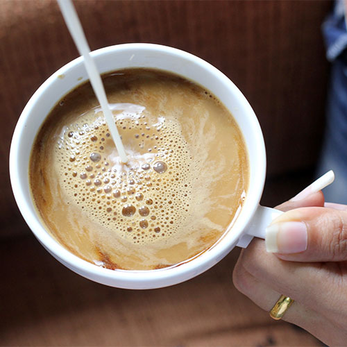 pouring creamer into coffee