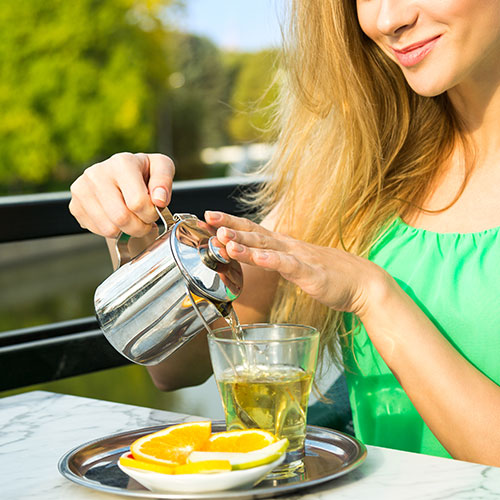 woman pouring cup of green tea