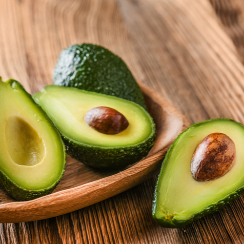 ripe avocados halved with pits inside